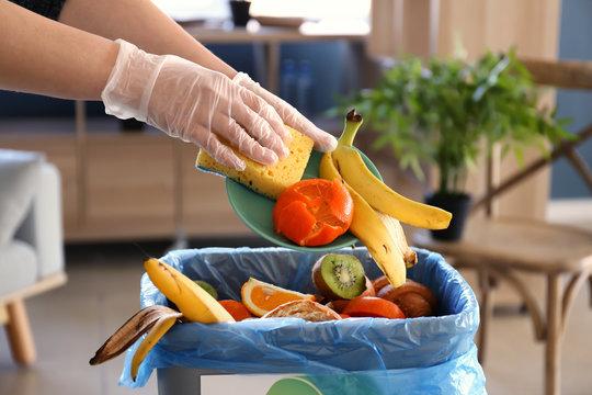 Woman throwing garbage into trash bin