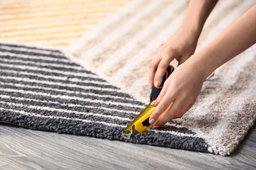 Woman with tape measure cutting carpet on floor