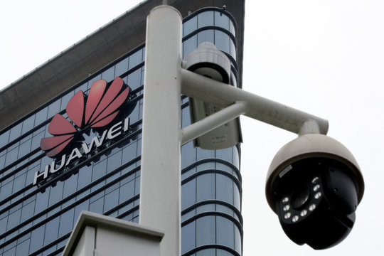 Surveillance cameras are seen in front of Huawei logo outside its factory campus in Dongguan, Guangdong province