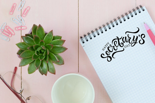 Feminine desk workspace with succulent, glasses, cup for coffee and notebook. Hand written lettering Happy Secretary's day