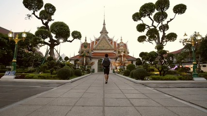 Wall Mural - A man traveler is walking and traveling in Wat Arun in Bangkok, Thailand.