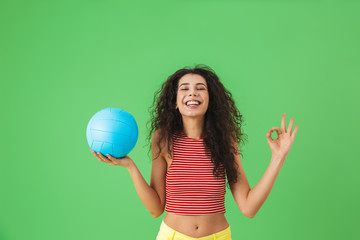 Image of joyful woman 20s wearing summer clothes smiling and holding volley ball