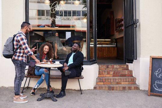 Group of smiling friends talking together at a sidewalk cafe
