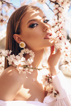beautiful young woman in elegant dress and luxurious earrings posing in garden with flowering peach trees