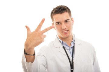 Portrait of young handsome doctor showing number three gesture