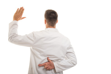 Back view of young doctor showing like gesture