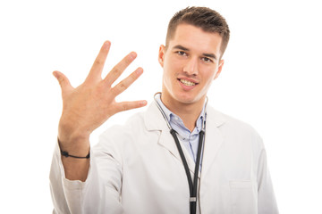 Portrait of young handsome doctor showing number five gesture