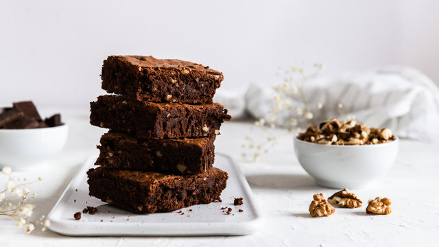 A stack of chocolate brownies on white background, homemade bakery and dessert. Bakery, confectionery concept. Side view, copy space