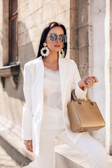 Obraz beautiful woman with dark hair in elegant white suit and coat, with accessories - fototapety do salonu