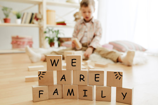 Wooden cubes with words WE ARE FAMILY in hands of happy smiling little boy at home. Conceptual image about child rights, education, childhood and social problems.