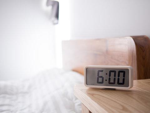 Digital alarm clock display 6 AM on the wood table,In the bedroom.