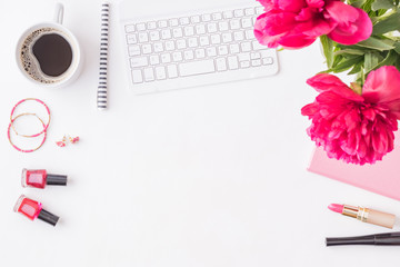 Flat lay blogger or freelancer workspace with a notebook, keyboard, red peonies on a white background