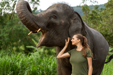 girl standing near an elephant in the jungle