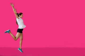 girl sportsman posing on a pink background