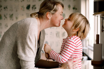 Mother and daughter rubbing noses in kitchen