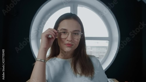 712fa577b869 The girl straightens her glasses, smiling, looking at the camera. Brunette  in a white t-shirt. Teen student. Slow motion. 4K.