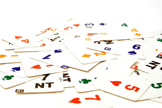 Cards for bridge of different colors on a white background. Equipment for a sports game of bridge. Betting concept. Corruption in sports. A bribe in the game, a bribe in real life.