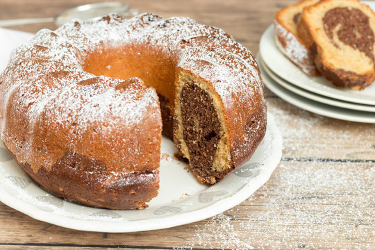 Marble cake with powdered sugar on top, wooden background