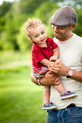 Happy Father Holding Toddler Son Outside - Color Portrait