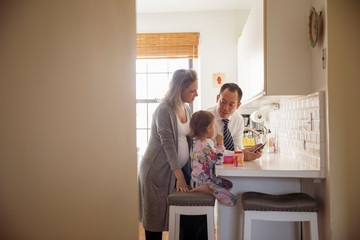 Father with smart phone talking to family in kitchen at home