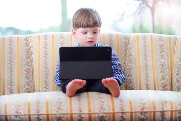 Ein kleiner Junge bedient ein ipad