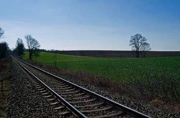 Reichstaedt / Germany: View over a straight single-track railway line in the hilly rural landscape in Eastern Thuringia on a sunny day in March