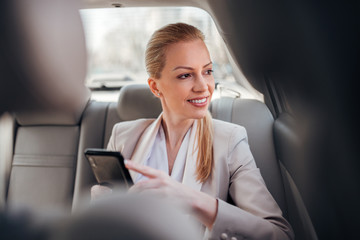 Positive businesswoman using phone and looking through car window.