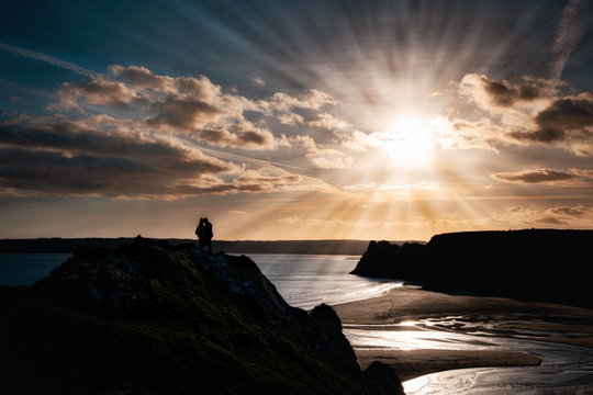 The Silhouette of a couple in a Romantic moment overlooking the Three Cliffs Bay at sunset, Swansea, Wales, UK