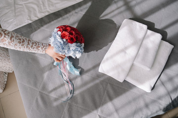 the bride puts the wedding bouquet on the bed.