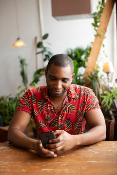 Man using smart phone on wooden table at home