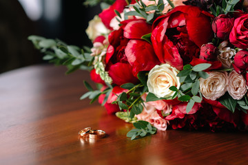 the bride's bouquet of red roses and wedding rings are on the table