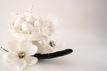 white romantic  Easter scene, cake stand with eggs, flowers and butterfly against white background, space for text