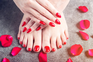 Young lady is showing her red manicure and pedicure nails