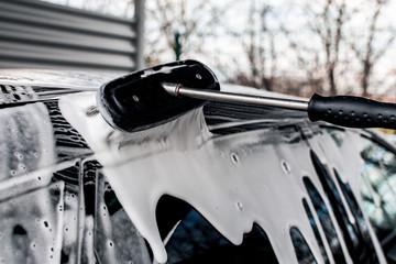 professionelle Autowäsche in einer Waschstraße- Mann reinigt den lack eines Fahrzeuges mit wasser und schaum_ professional car wash in a car wash man cleans the paint of a vehicle with water and foam