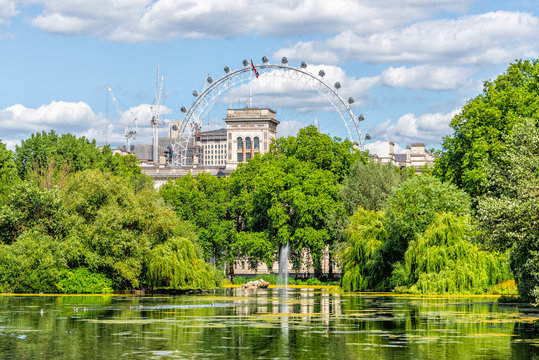 London Eye cityscape view building with St James Park green lake pond on summer day and water fountain in UK