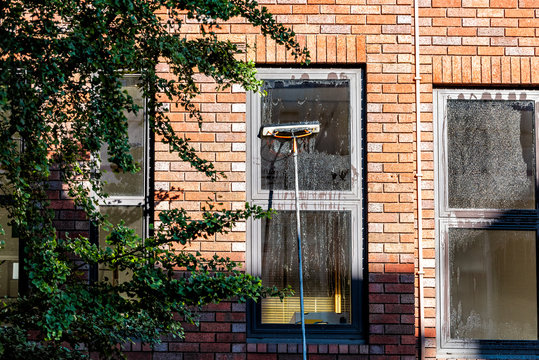 Worker cleaning washing windows on brick apartment flat with soap and water in London, UK neighborhood city
