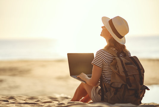 young woman working with laptop on nature in beach