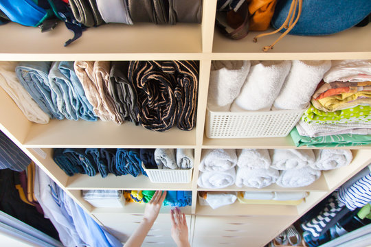 Woman folds clothes vertically on a wardrobe shelf. Japanese storage system.