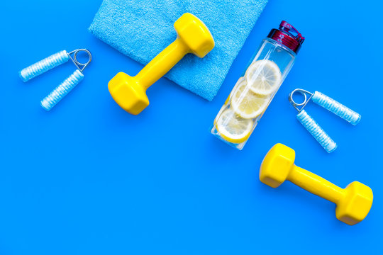 workout with bars, bottle of water, towel and wrist builder blue background top view copyspace