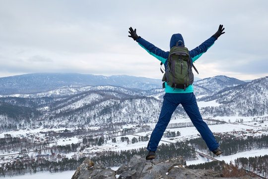 Young Female girl with backpack in the mountains jumping in mid air with hands up and snowy winter mountains in the background. hike tourist in the mountains. Adventure