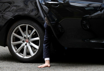 Britain's Conservative Party Chief Whip Julian Smith reaches for his dropped phone as he sits inside his car outside Downing Street in London
