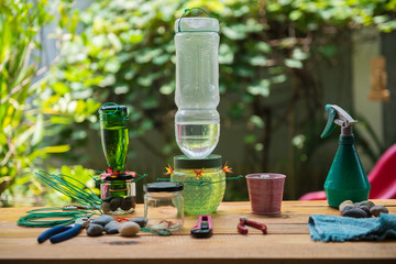 DIY making hummingbird feeder in the garden with tools on the wooden bench