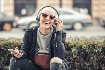 Young modern woman with bald hairstyle listening to her favorite music over her big green headphones, outdoor urban scene