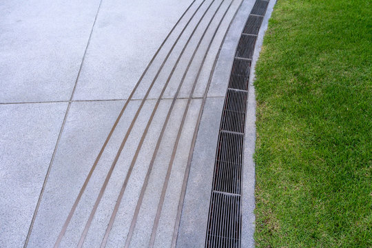 Curve water drain or ditch on the road. Gutters drain grate, drain cover.