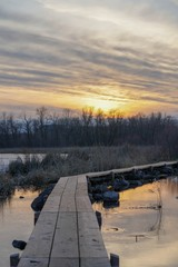 Idyllic sunset over a wood trail at the wetlands in a park