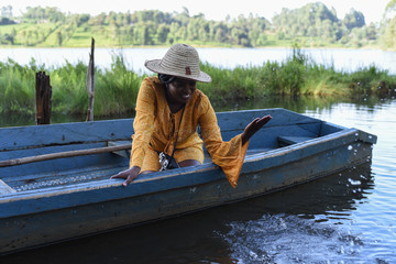 Woman with a hat playing in a boat in Kenya