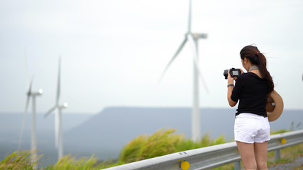 Asian women tourists are taking a picture of a wind turbine at a scenic spot.