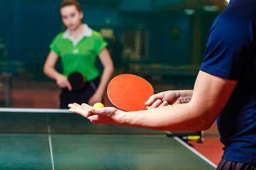 the coach teaches a teenage girl to play table tennis. Filing the ball in ping pong
