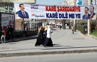 Women walk past an election banner written in Kurdish, that has pictures of President Tayyip Erdogan and Mayor Cumali Atilla on it, in Diyarbakir