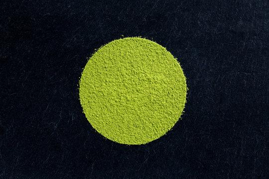 matcha green tea powder on black slate background
